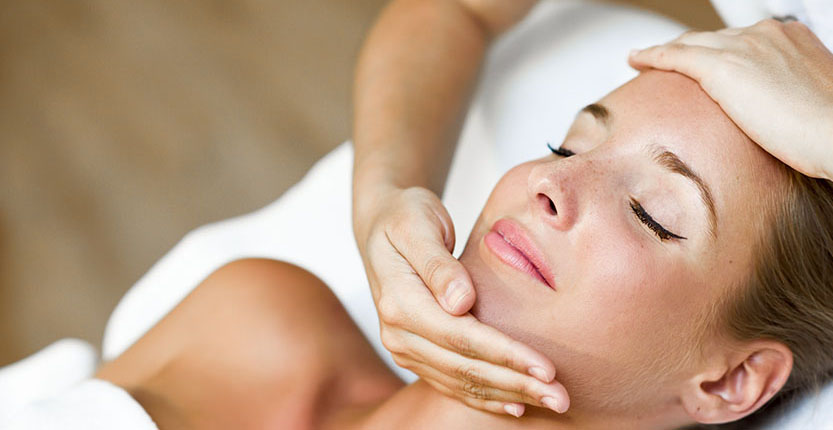 Young blond woman receiving a head massage in a spa center with eyes closed. Female patient is receiving treatment by professional therapist.