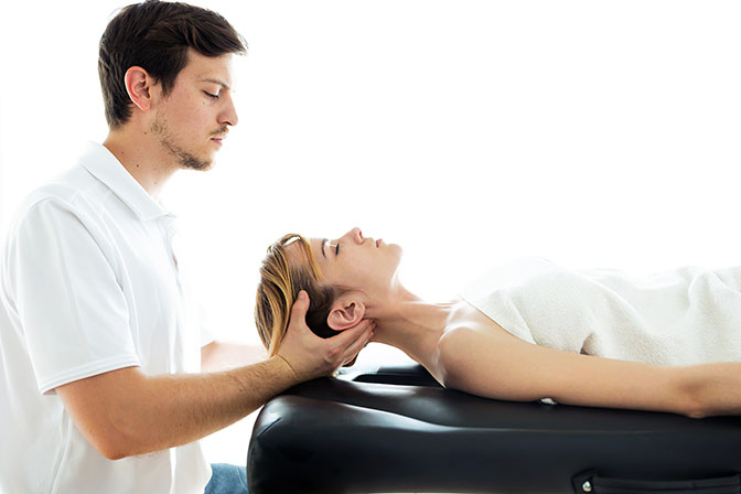 Shot of young physiotherapist doing a neck treatment to the patient in a physiotherapy room. Rehabilitation, medical massage and manual therapy concept.