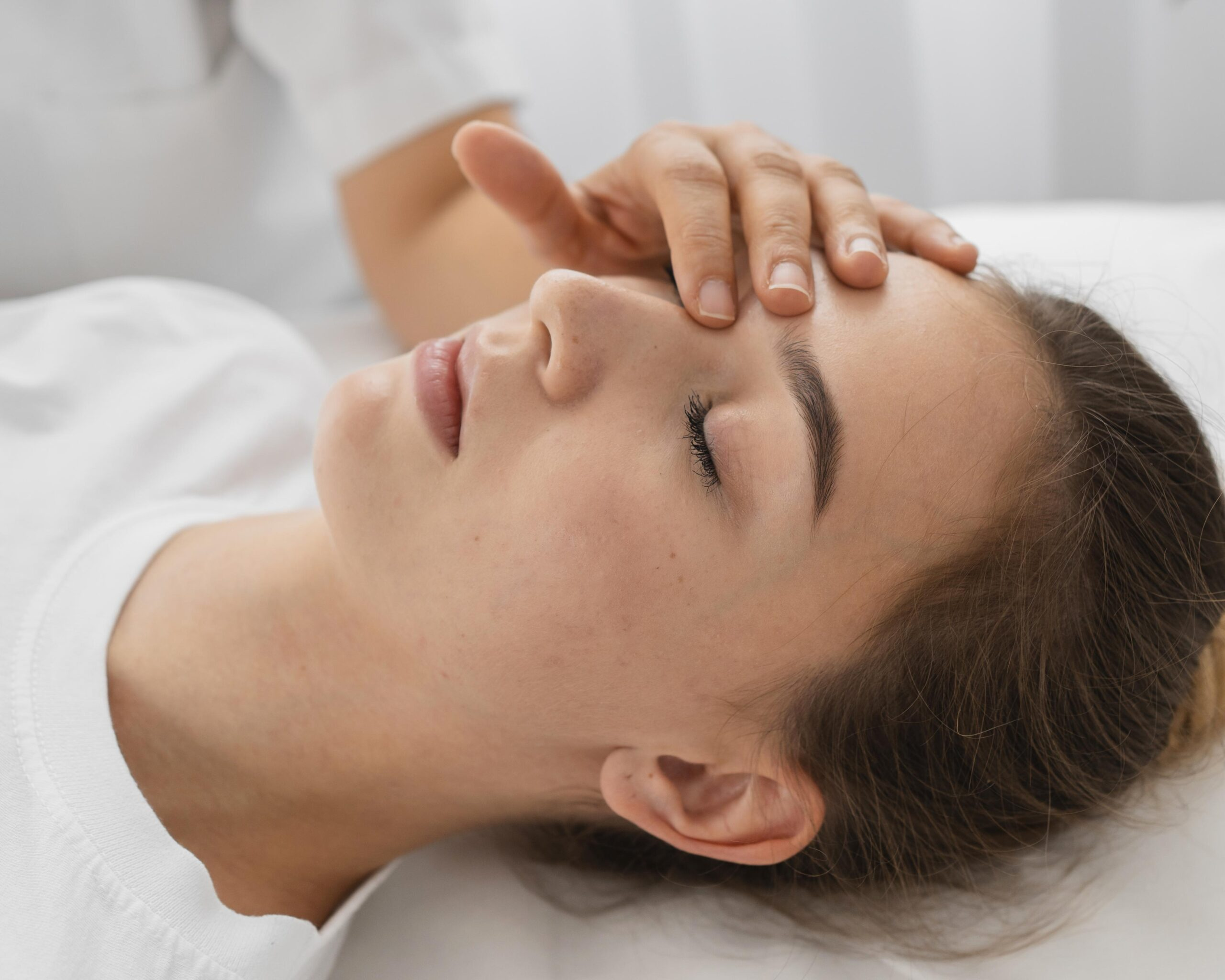 osteopathist-treating-female-patient-by-massaging-her-face-close-up